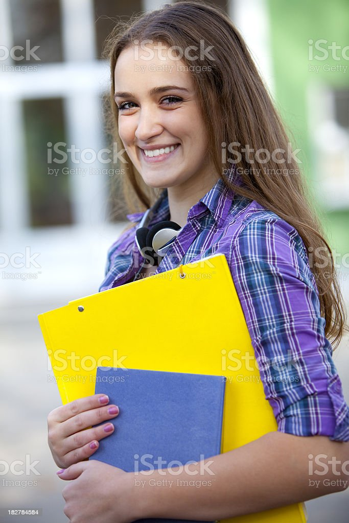 Young female student standing in front of school royalty-free stock photo