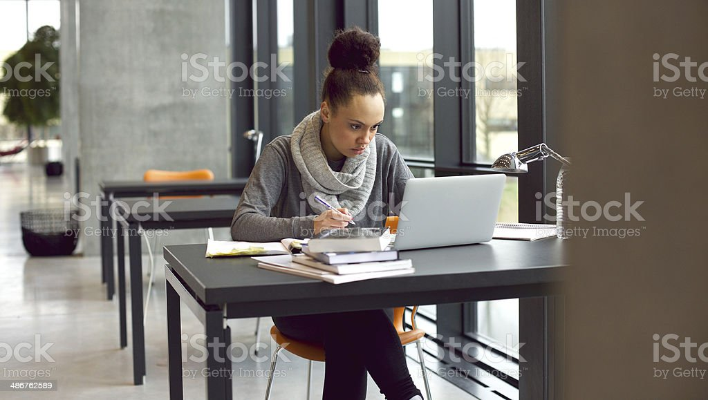 Young female student taking notes for her study stock photo