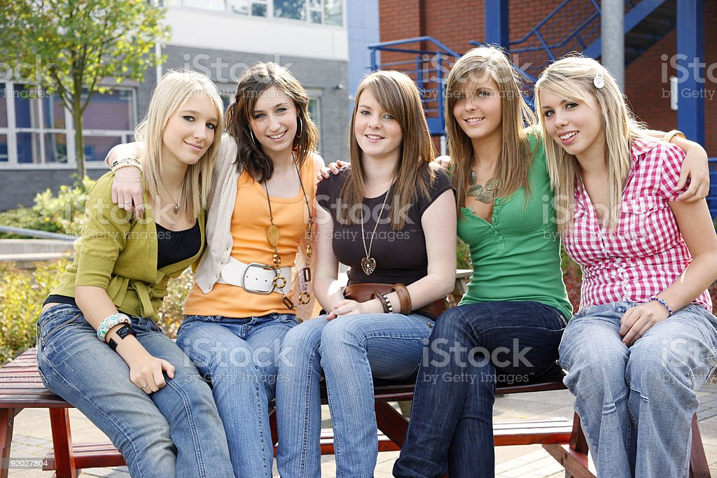 Young female students sitting outside school campus royalty-free stock photo