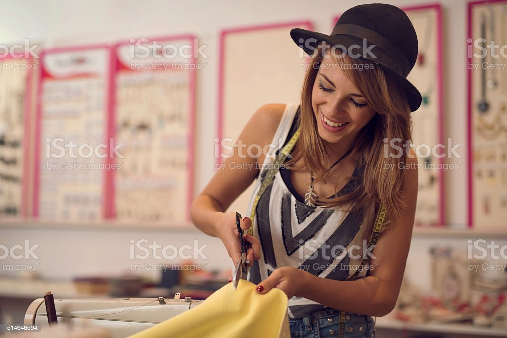 Young female tailor cutting material in a design studio. stock photo