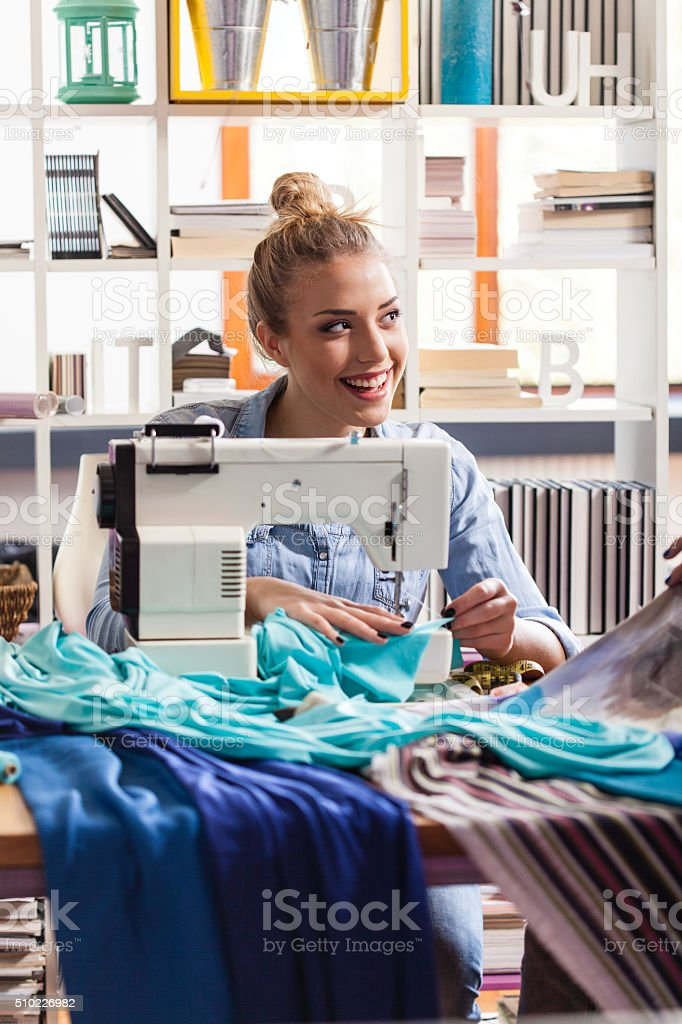 Young female tailor stitching cloth on sewing machine stock photo