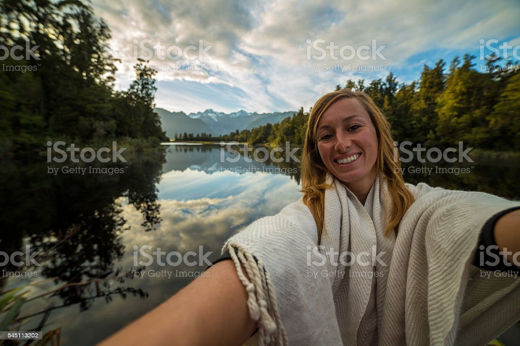 Young female takes selfie portrait at lake Matheson, Mount Cook stock photo