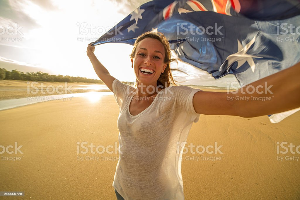 Young female takes selfie portrait on beach with flag stock photo