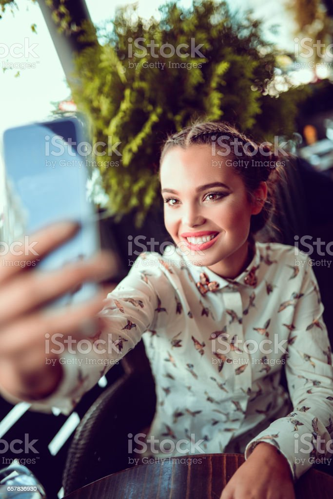 Young Female Taking Selfie at her Favorite Coffee Shop stock photo