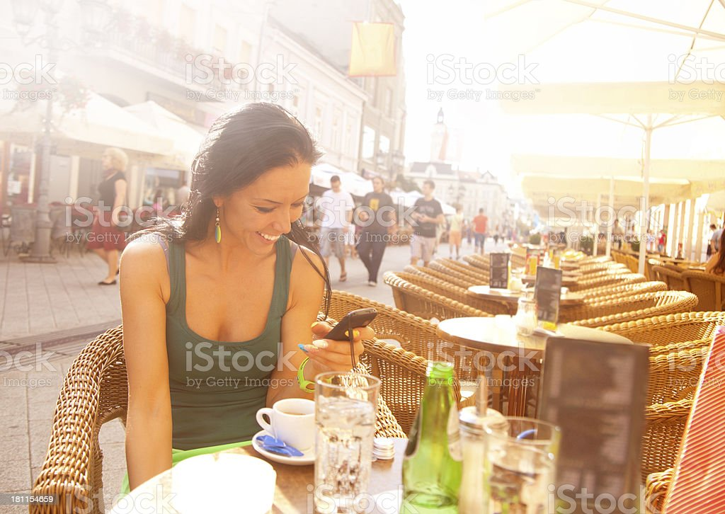 Young female talking on cell phone while having coffee royalty-free stock photo