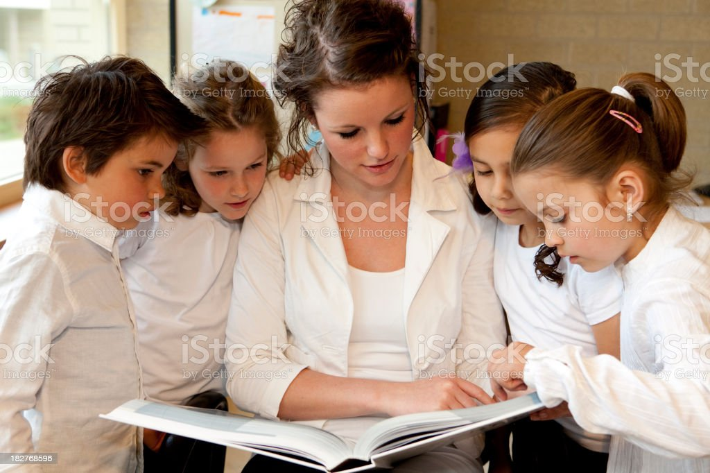 Young female teacher reading a story royalty-free stock photo