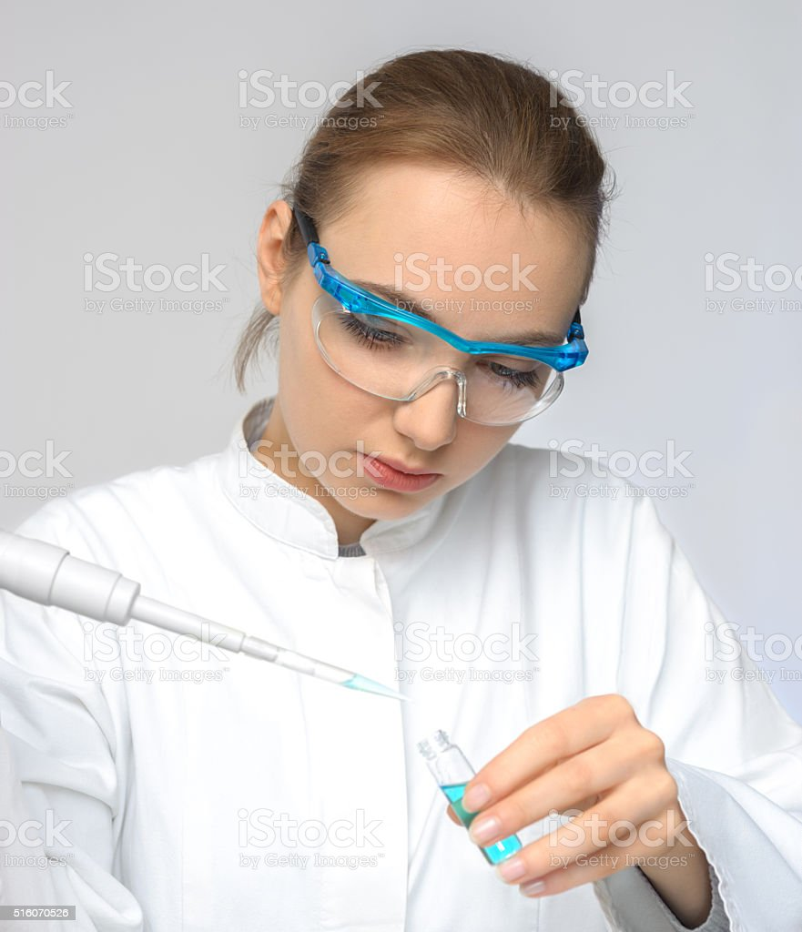 Young female tech or scientist loads liquid sample stock photo