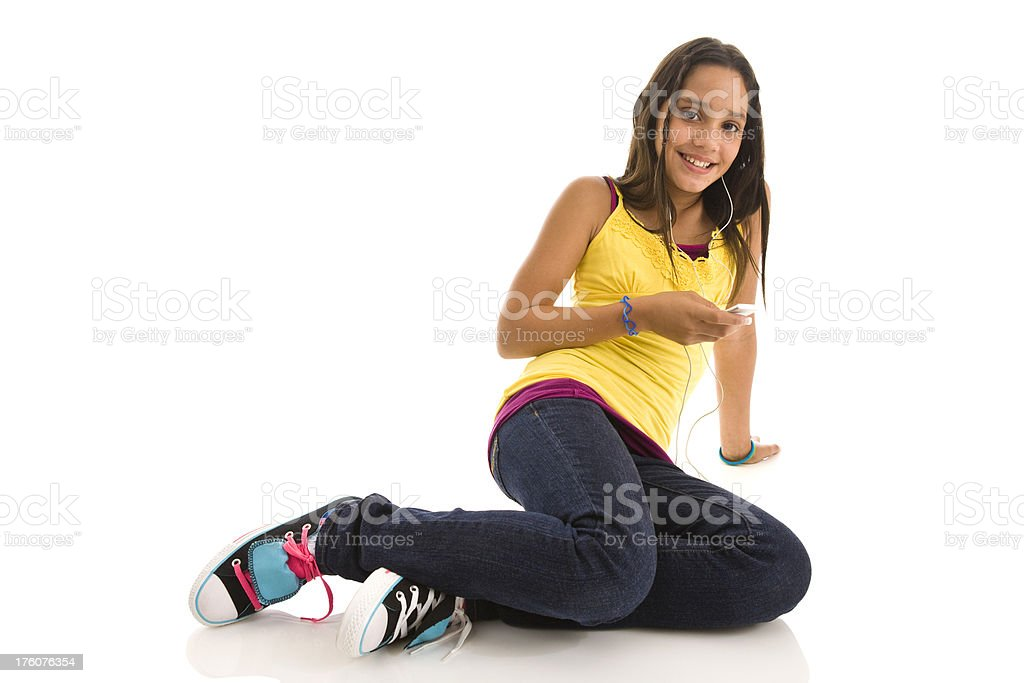 Young female teenager with MP3 player sitting on floor royalty-free stock photo