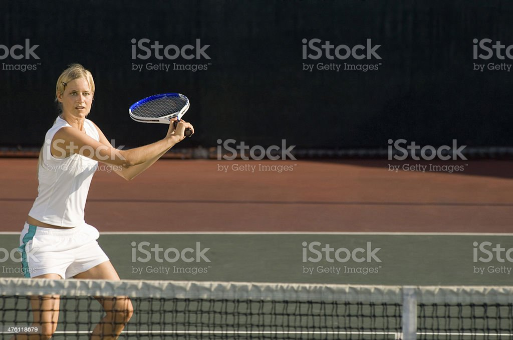 Young female tennis player swinging racket at court stock photo