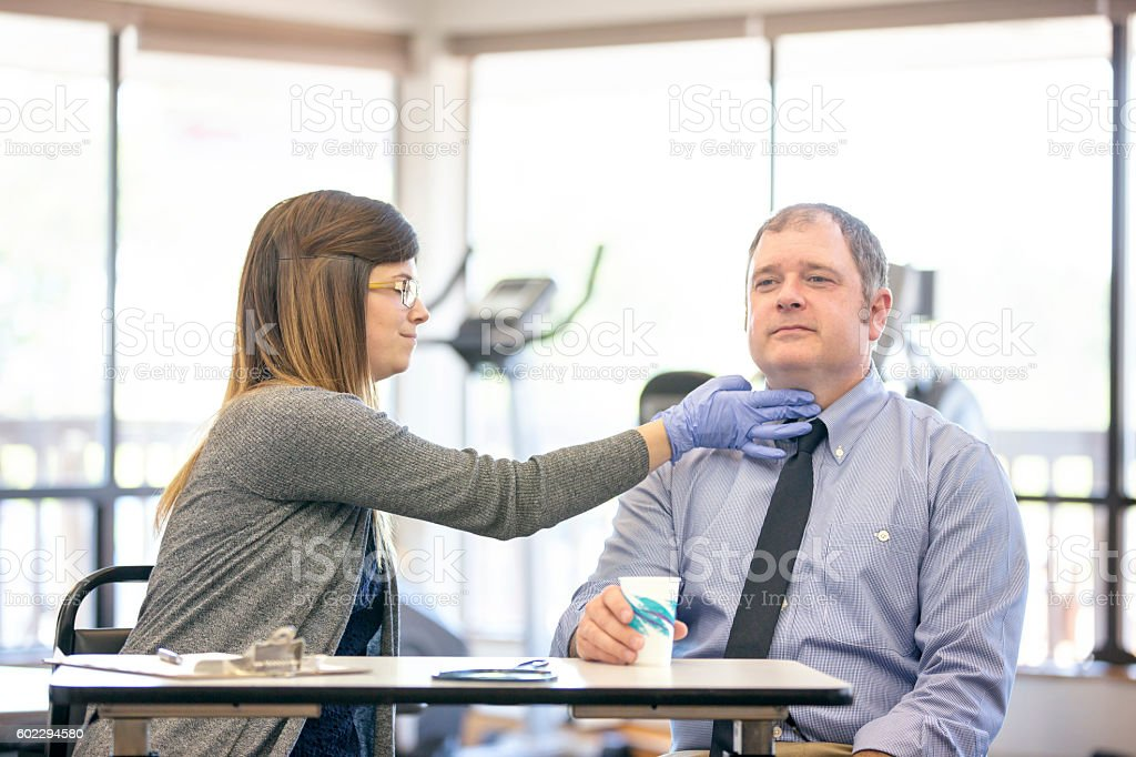 Young female therapist taking vitals on an adult male stock photo