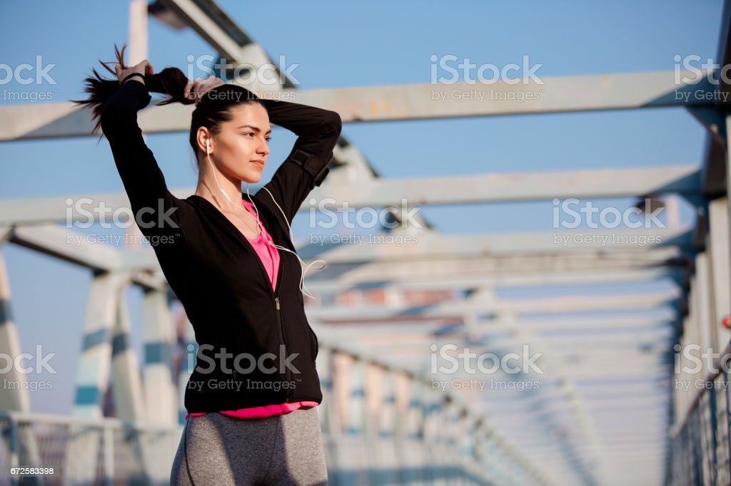 Young female ties the tail and preparing for running stock photo