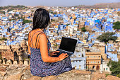 Young female tourist using laptop, Jodhpur, India