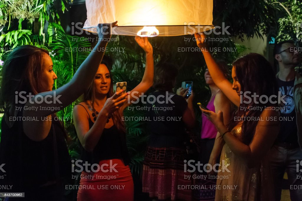 Young female tourists release a floating lantern in Chiang Mai, Thailand stock photo