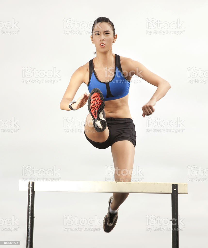 Young Female Track Athlete Jumping Hurdles royalty-free stock photo