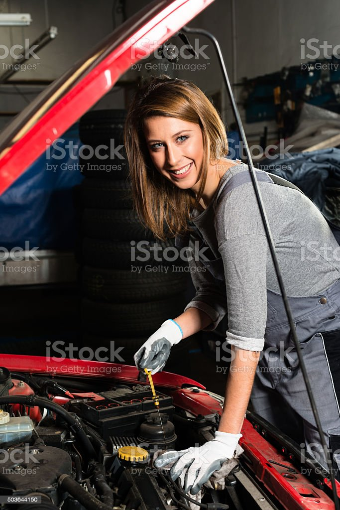 Young female trainee fixing car engine in garage stock photo