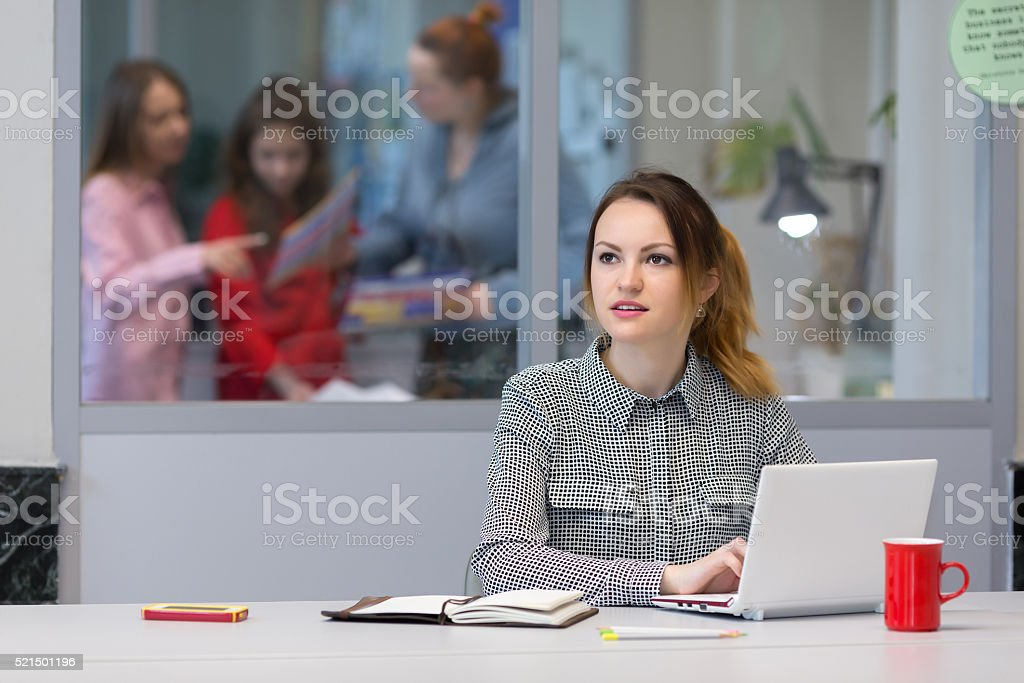 Young female Trainee working on Laptop in Office Interior stock photo
