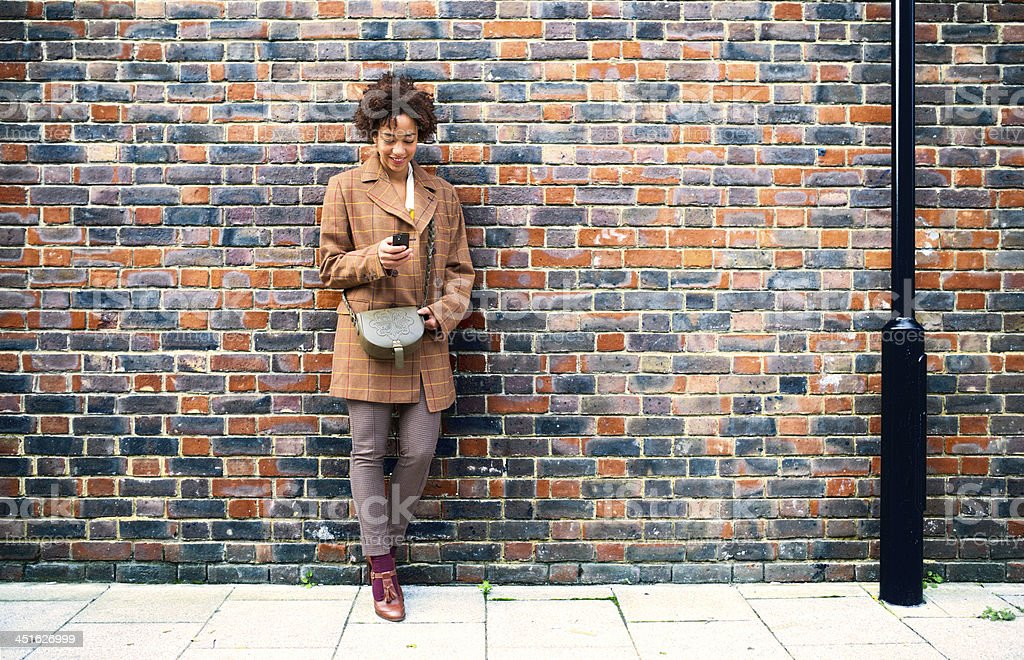 young female using her phone while leaning on the wall stock photo