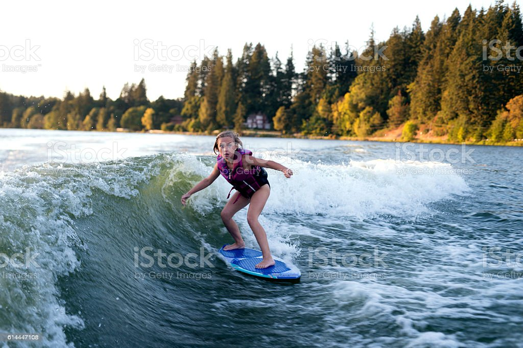 Young female wake surfing behind a ski boat stock photo