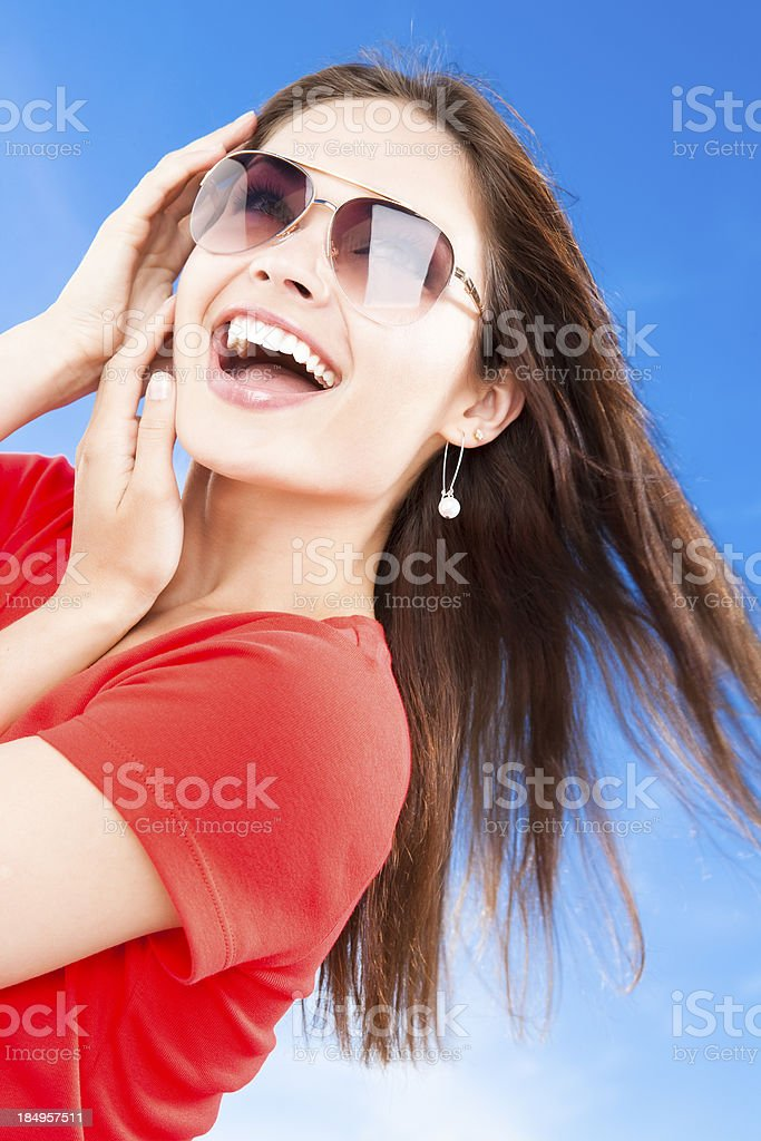Young female wearing sunglasses against blue sky royalty-free stock photo