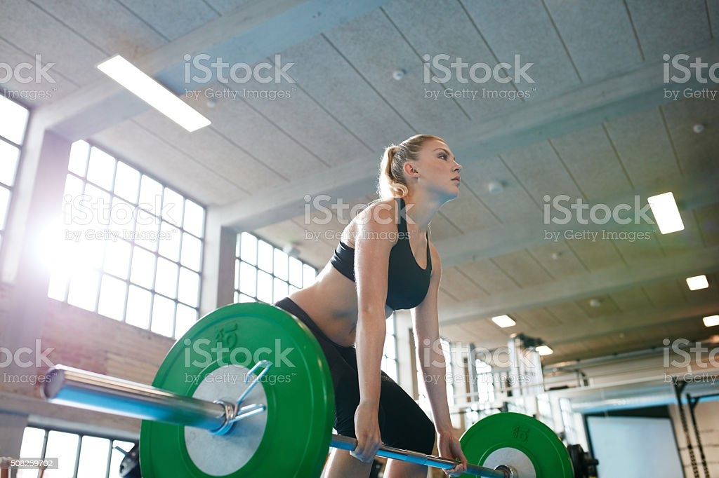 Young female weightlifter focusing before the lift stock photo
