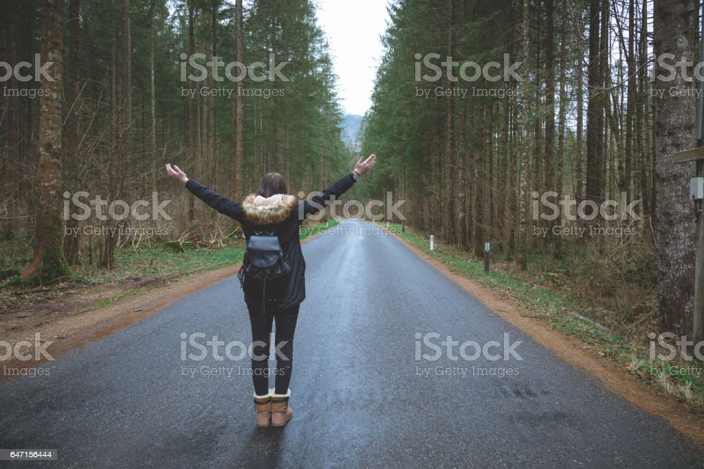 Young female with arms outstretched on a road stock photo