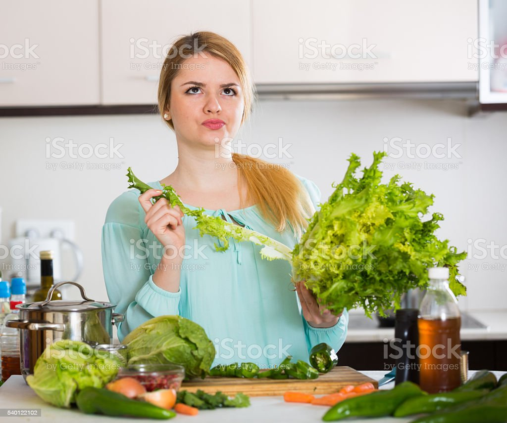 Young female with rotten vegetables at home stock photo