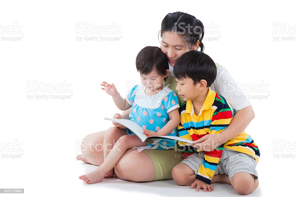 Young female with two little asian children reading a book stock photo