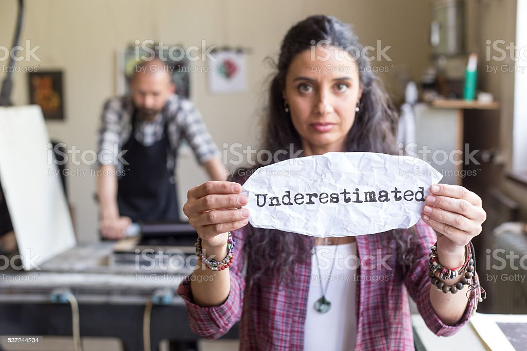 Young female worker holding a sign 'underestimated' stock photo