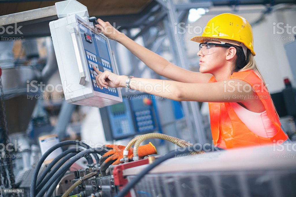 Young female worker operating a machine in factory stock photo