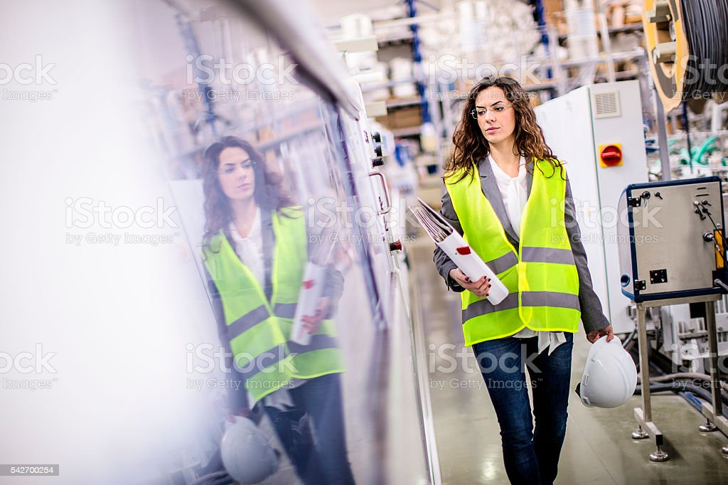 Young female worker walking through the factory stock photo