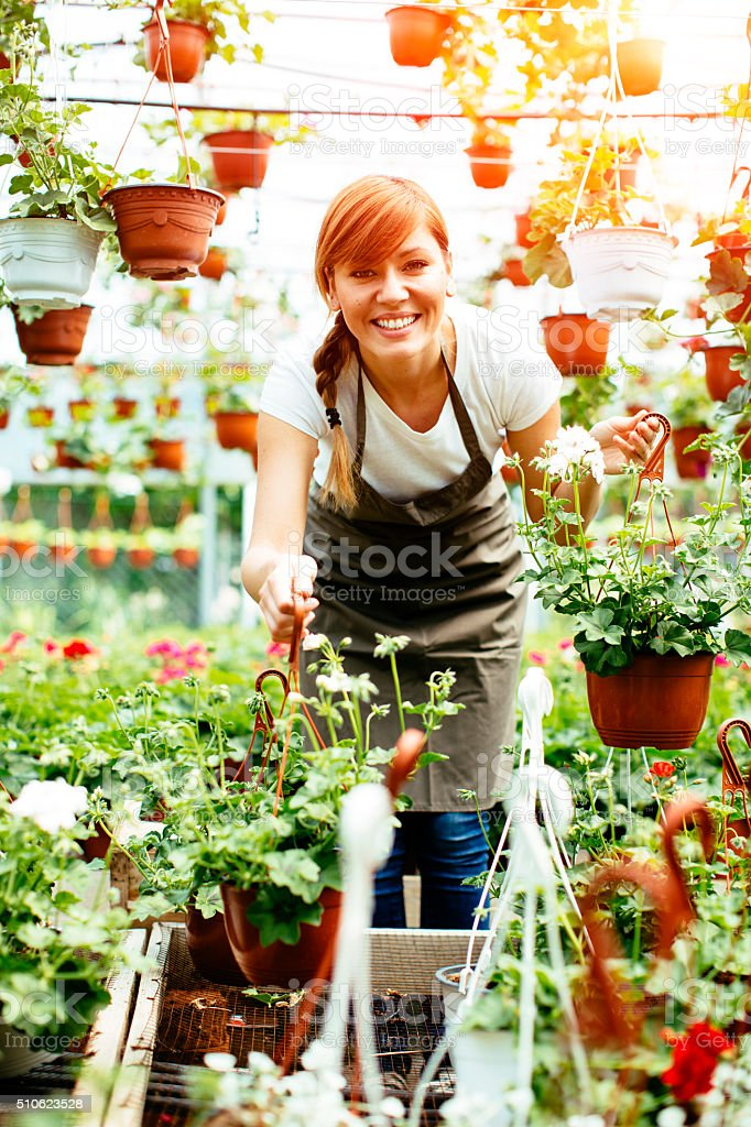Young Female Working At Plant Nursery stock photo