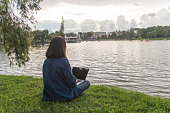 Young female writer sitting beside the lake using laptop