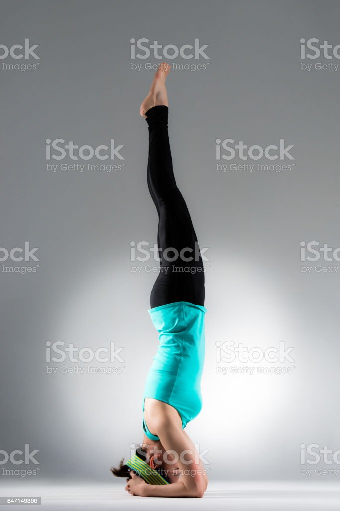 young female yoga student handstand on floor stock photo