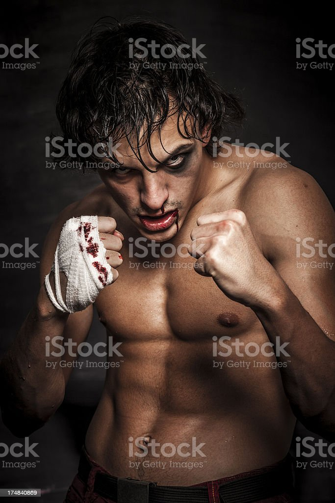 Young fighter posing over black background royalty-free stock photo