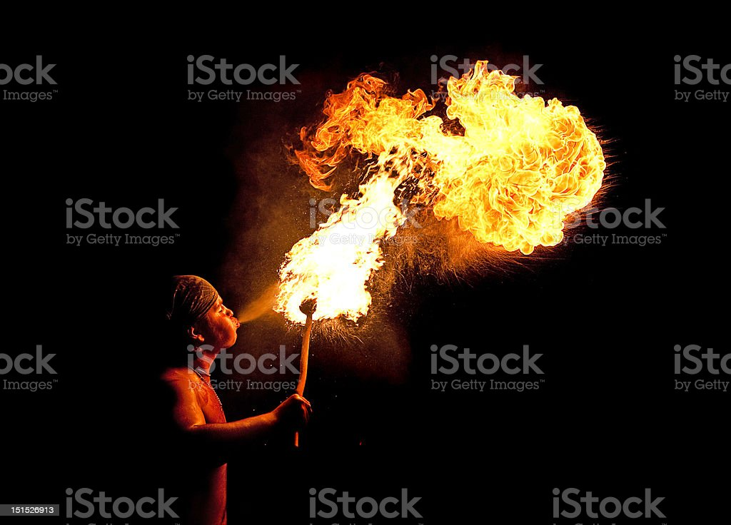 Young fireblower and flames on black background royalty-free stock photo