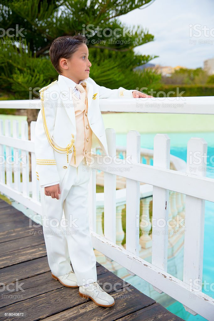 Young First Communion boy leaning on a white wooden fence stock photo