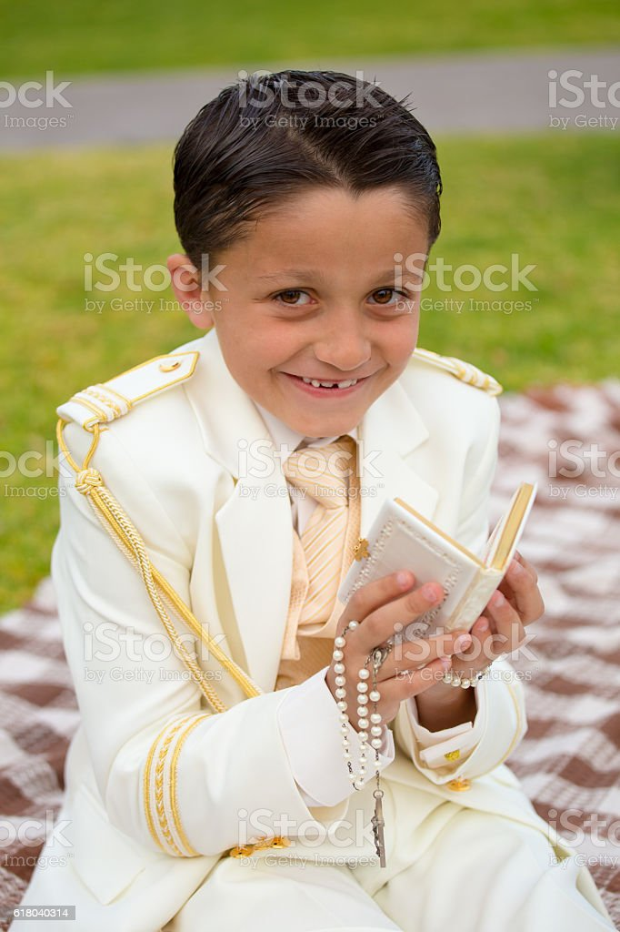 Young First Communion boy smiling with prayer book and rosary stock photo