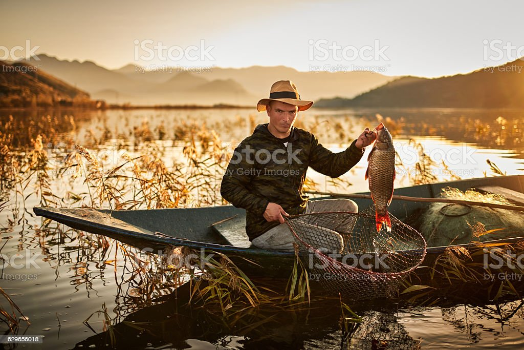 Young fisherman at sunset stock photo
