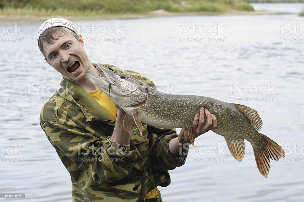 Young fisherman holds big pike stock photo