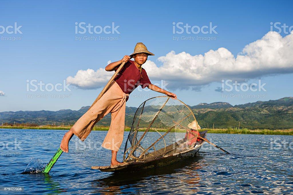 Young fisherman in boat on Inle Lake, Myanmar stock photo