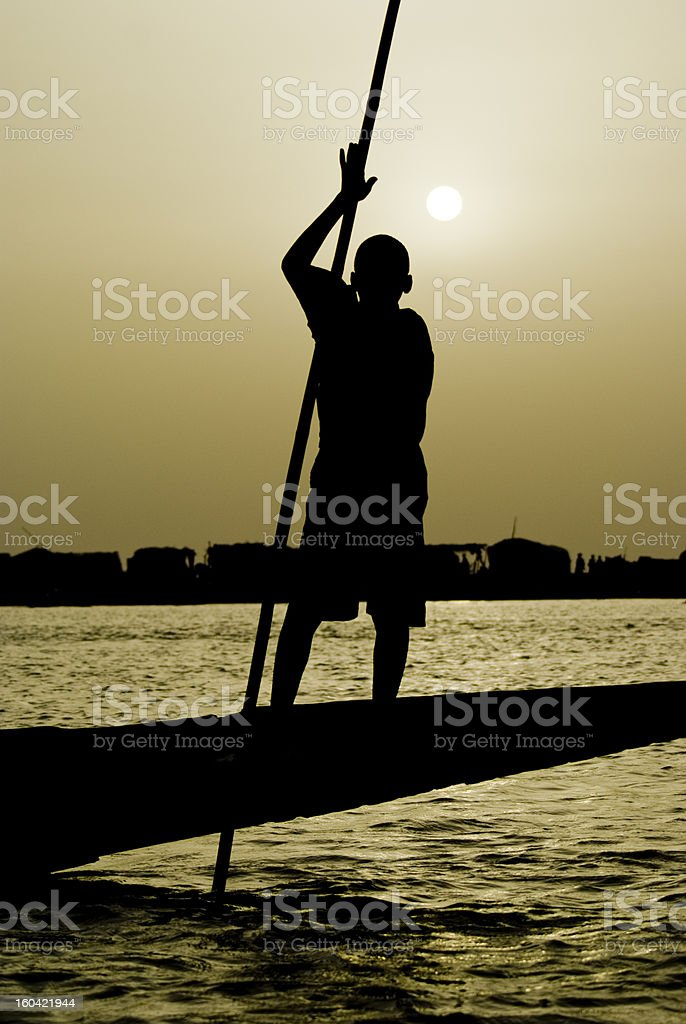 Young Fisherman over pinasse, Niger's River. stock photo
