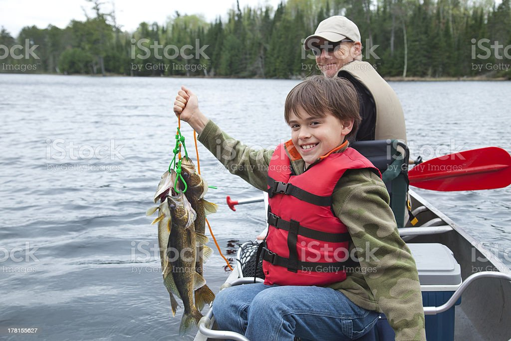 Young fisherman proudly holds stringer of walleyes royalty-free stock photo