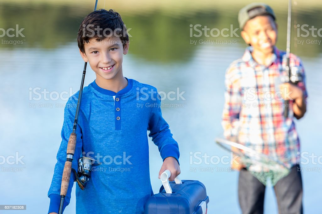 Young fishing buddies prepare to fish in pond stock photo