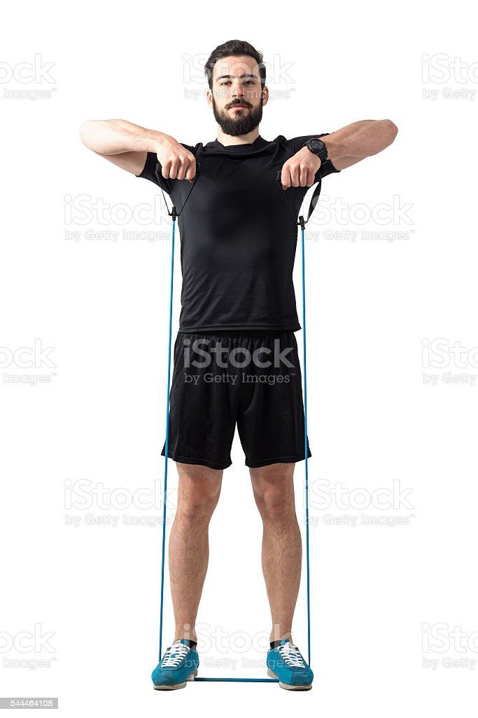 Young fit athletic man shoulder exercising with resistance bands stock photo