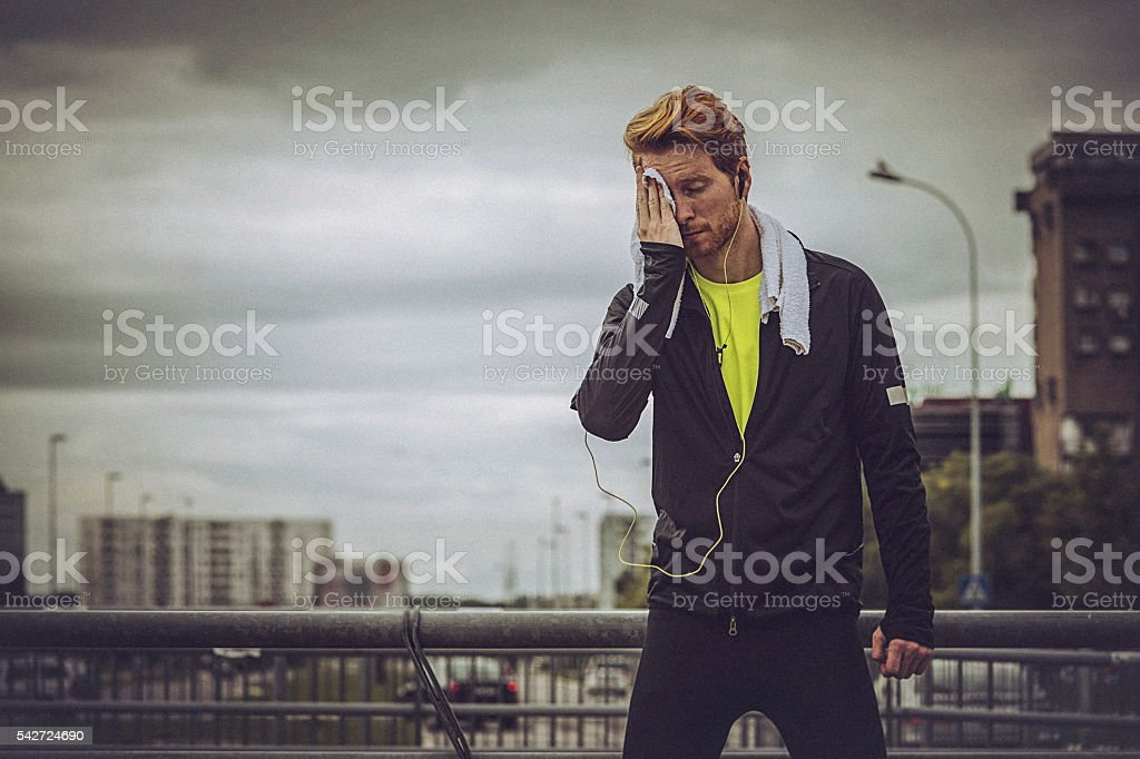 Young fit man relaxing on the stairs, after strenuous workout stock photo