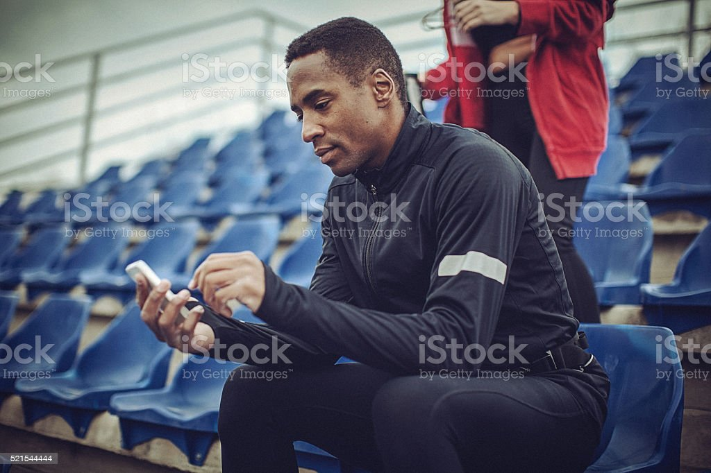 Young fit man texting at the stadium after strenuous workout stock photo