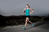 young fit sport woman running outdoors on asphalt road