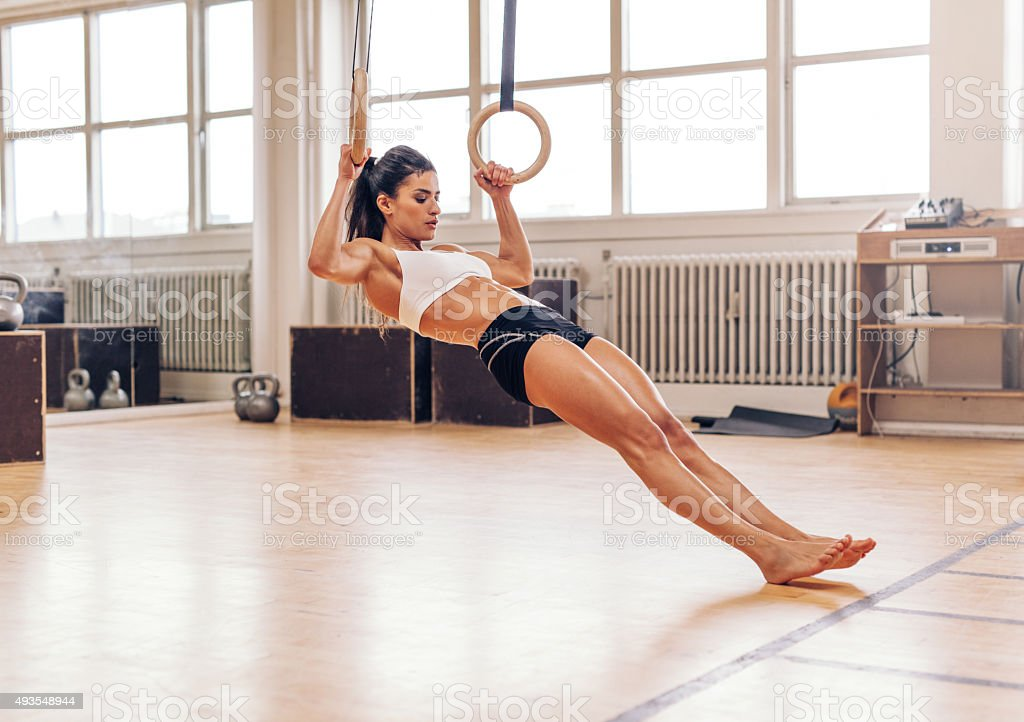 Young fit woman doing pull-ups on gymnastic rings stock photo