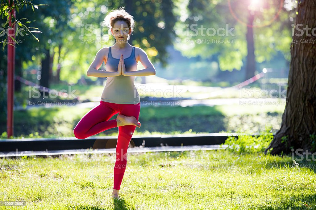 Young fit woman doing yoga exercises stock photo
