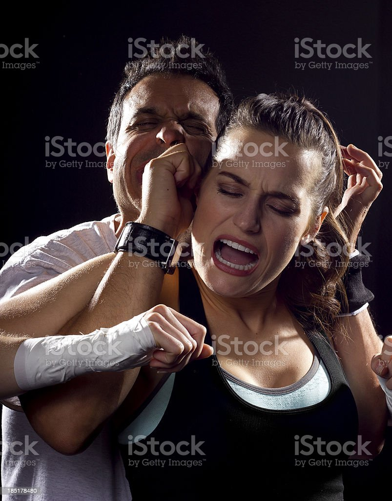 Young Fit Woman Fighting a Man on a Black Background royalty-free stock photo